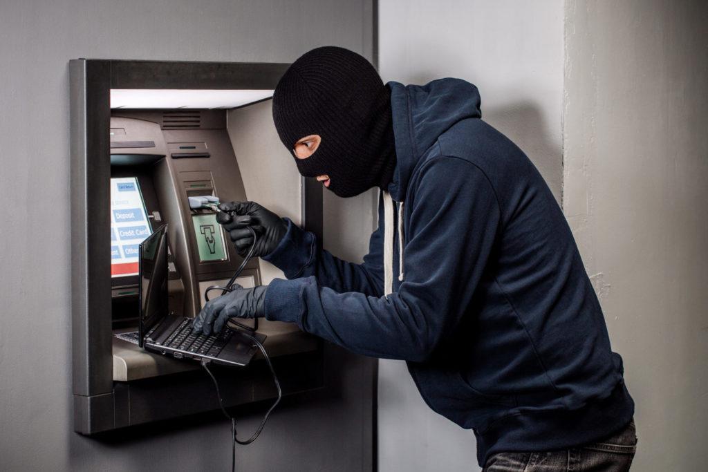 homme masqué piratant un bancomat