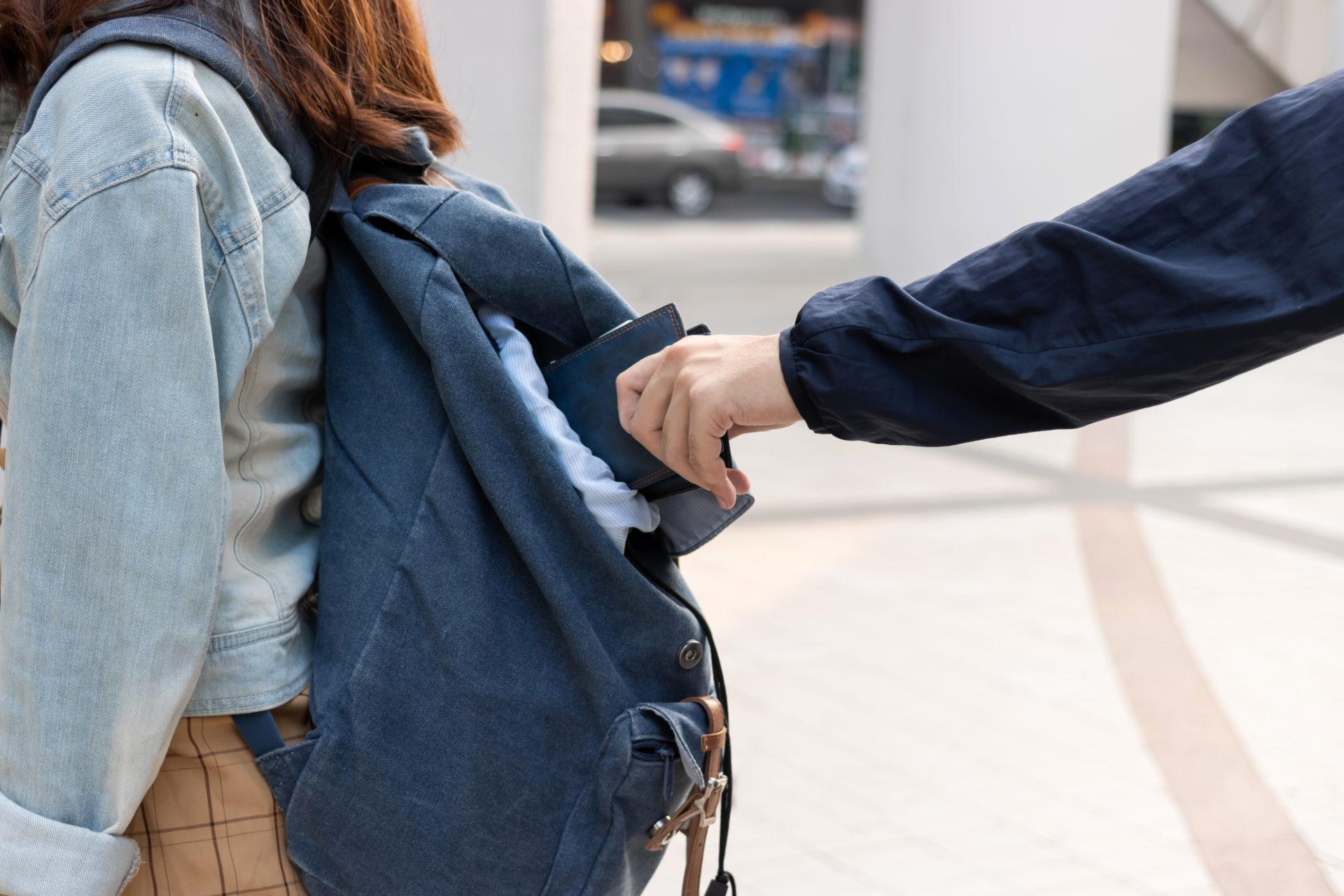 homme dérobant un porte-monnaie dans un sac à dos